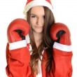 Christmas woman hitting wearing boxing gloves and red santa hat - Photo