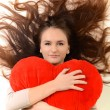 Lovely woman with red heart-shaped pillow — Stock Photo