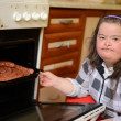 Attractive down syndrome woman cocking in the kitchen - Stockfoto