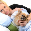 A happy young woman lying on her bed with her puppy. — Stock Photo