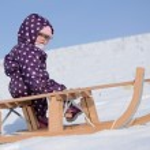 Little girl rolls sleigh in winter on snow. — Stock Photo #20428223