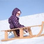 Little girl rolls sleigh in winter on snow. — Stock Photo #20428277