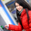 Stock Photo: Womwithdrawing money from credit card at ATM