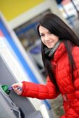 Woman withdrawing money from credit card at ATM — Stock Photo