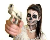 Girl with painting dead mask skull with gun — Stock Photo