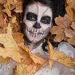 Girl with painting dead mask skull with leaves — Stock Photo