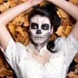 Girl with painting dead mask skull with leaves — Lizenzfreies Foto