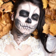 Royalty-Free Stock Photo: Girl with painting dead mask skull with leaves