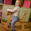 Little girl rides a toy rocking - Stock Photo