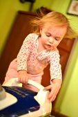 Baby with vacuum cleaner in living room — Stock Photo