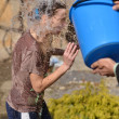 Man pours water on a girl out of the bucket — Stock Photo #23304400