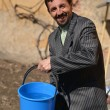 A man with a bucket of water — Stock Photo