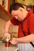 Down syndrome man cocking in the kitchen — Stock Photo