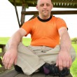 Down syndrome man sitting - Stock Photo