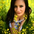 Girl in a field of yellow flowers — Stock Photo
