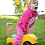 Cute girl in a little car — Stock Photo
