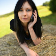 Girl lying on hay with mobile phone — Stock Photo