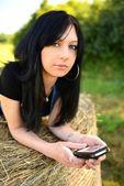 携帯電話と干し草に横たわった少女 — ストック写真