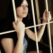 Stock Photo: Female Criminal Behind Bars