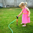 Stock Photo: Cute curly girl watering flowers in the garden