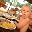 Beautiful laughing little girl eating French fries — Stock Photo
