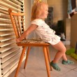 Foto Stock: Baby girl sitting on chair