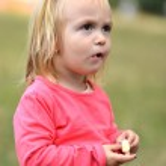 Little girl eating corn nibbles — Stock Photo #31248281