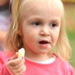 Little girl eating corn nibbles — Stock Photo #31248365