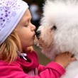 Children girl kissing her puppy — Stockfoto