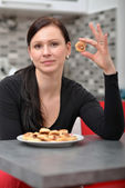 Woman eating cookies — Stockfoto