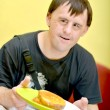 Stock Photo: Mwith down syndrome eating