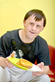 Man with down syndrome eating — Stock Photo