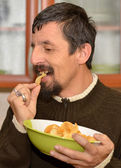 Portrait of young brunette man eating chips — Stock Photo