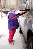 Baby cleaning the car from snow — Stock Photo
