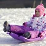 Portrait of happy girl in winter fun, snow, family sledding — Stock Photo #39101521