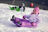 Portrait of happy girl in winter fun, snow, family sledding — Stock Photo