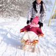 Mother and daughter sledging, nice winter scene — Stock Photo #39874225