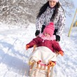 Mother and daughter sledging, nice winter scene — Stock Photo #39874247
