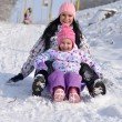 Stock Photo: Winter fun - family sledding