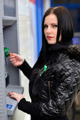 The girl draws out money in ATM — Stock Photo