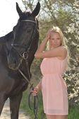 Dark horse and woman — Stock Photo