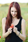 Woman holding a poppy flower — Stock Photo
