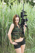Sexy woman holding up her weapon — Stock Photo