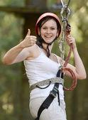 Happy girl climbing between trees — Stock Photo