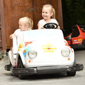 Two girls riding toy car — Stock Photo