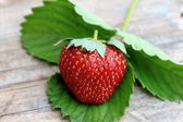 Fresh strawberry with green leaf on old wooden background — Stock Photo