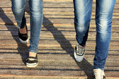 Female legs in jeans and sneakers closeup — Stock Photo