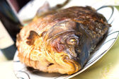 Baked carp in a plate with wine in background — Stock Photo