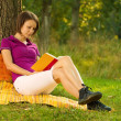 Beautiful young brunette reading in the park — Stock Photo