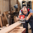 Carpenter with an electric router — Stock Photo #21131011